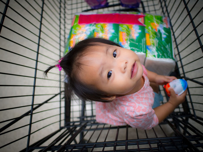 High angle portrait of girl sitting in shopping cart