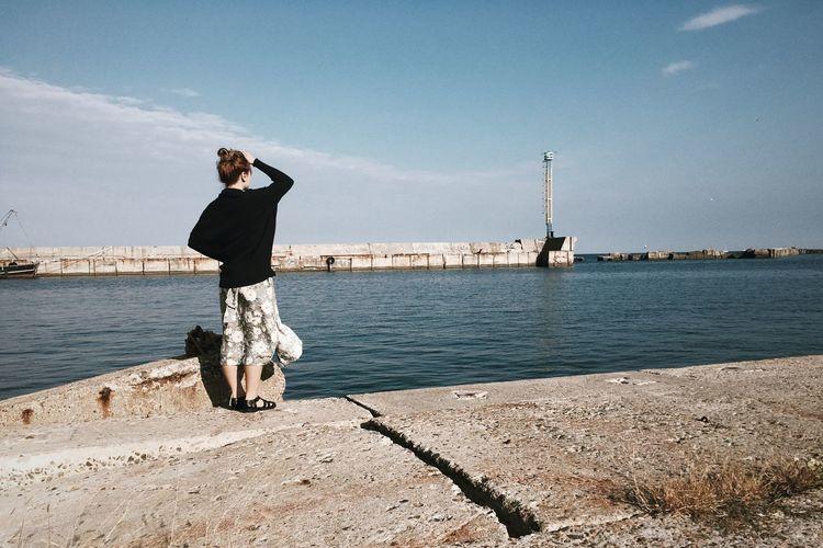 Full length of woman standing at promenade against sky
