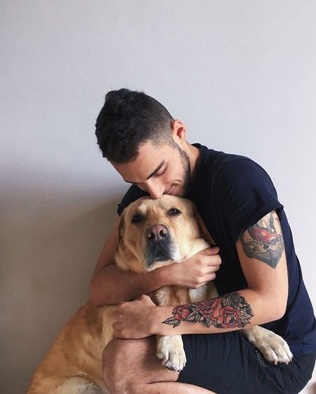 Man embracing dog against wall