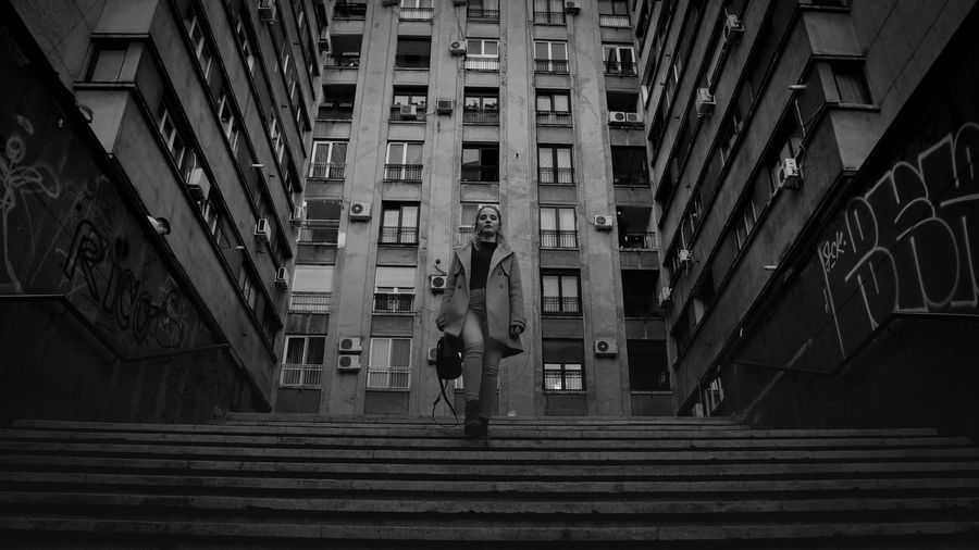 Low angle view of man standing on staircase amidst buildings