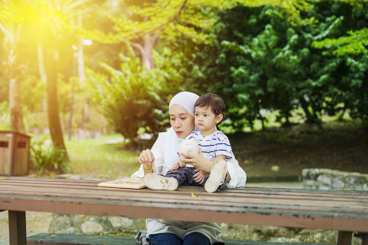 Young woman with her cute son learn how to put coins into piggy bank. Future planning concept. Child Childhood Togetherness Family Males  Men Bonding Son Innocence Sitting Two People Boys Bench Casual Clothing Leisure Activity Seat Park Real People Full Length Day Tree Park Bench Outdoors