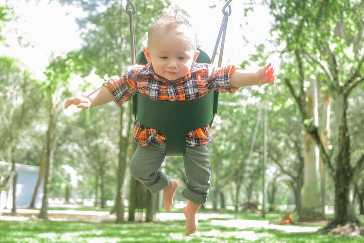 Baby boy in swing at park