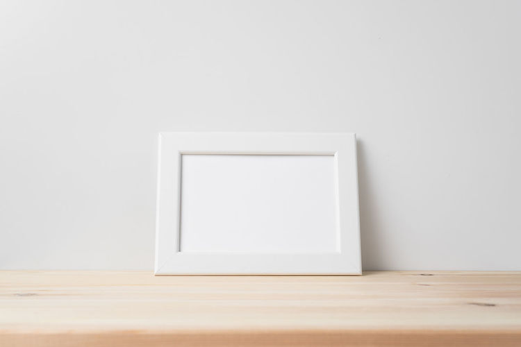 Close-up of empty table against white wall