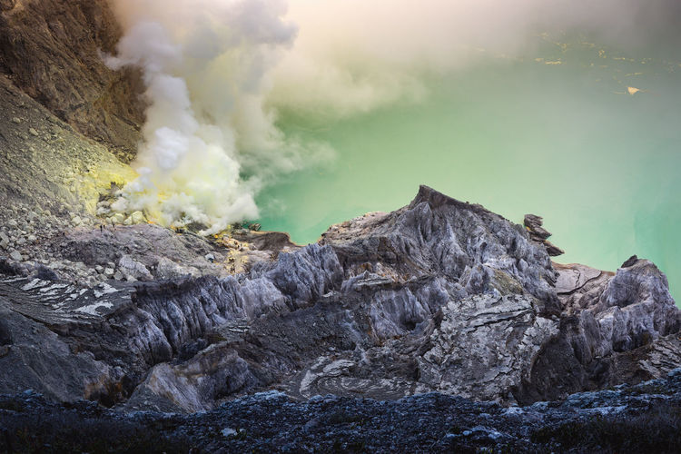 Landscape of Kawah Ijen volcano in sunrise scene of Indonesia. Smoke - Physical Structure Rock Mountain No People Day Nature Beauty In Nature Geology Rock - Object Solid Volcano Non-urban Scene Power In Nature Land Scenics - Nature Heat - Temperature Physical Geography Rock Formation Outdoors Emitting Volcanic Crater Formation INDONESIA Kawah Ijen