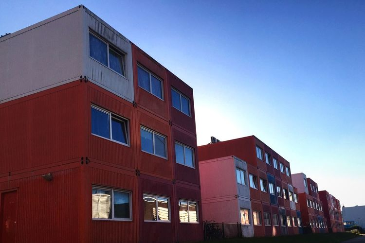 Exterior of red buildings in row against clear sky
