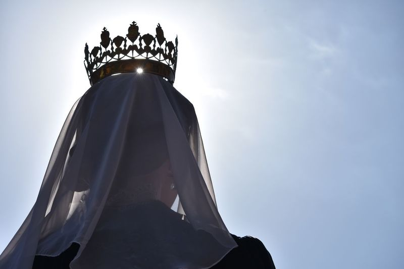 Low angle view of queen wearing crown against sky