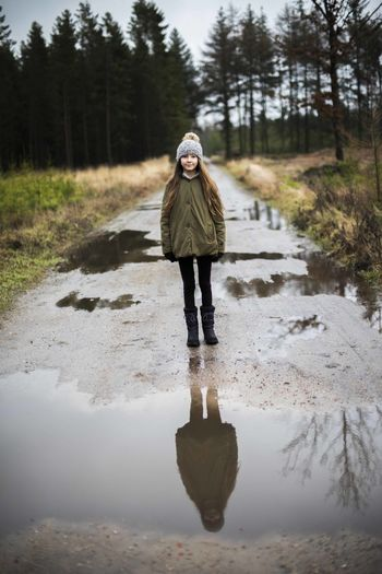 Portrait of girl standing on wet road