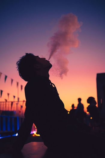 Young man smoking. Sky Sunset Silhouette Orange Color Nature Architecture Men People Outdoors Dusk Smoke - Physical Structure Purple City