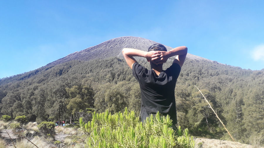 Rear view of man with arms raised on mountain against sky