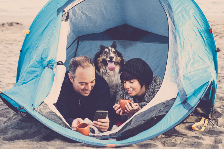 Couple Using Mobile Phone With Dog Relaxing In Tent At Beach