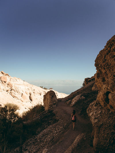 Rear View Of Woman Walking On Mountain Trail Against Clear Sky