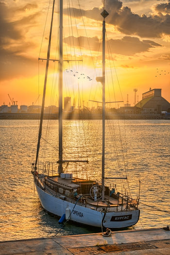 Sailboats moored on sea against sky during sunset