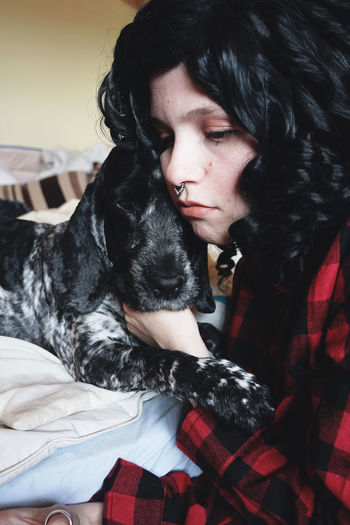 Close-Up Of Tensed Young Woman Holding Dog On Bed At Home