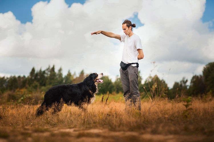 Man training dog on grassy land against cloudy sky
