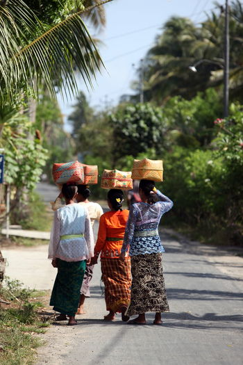 Rear view of women with whicker baskets walking on road