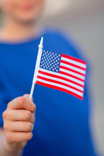 USA flag One Person Flag Holding Blue Patriotism Human Hand Hand Close-up Human Body Part Red Focus On Foreground Real People Pride Striped Men Finger Blue Background