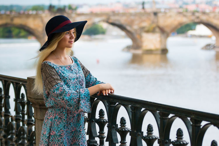 Beautiful woman standing by railing against river