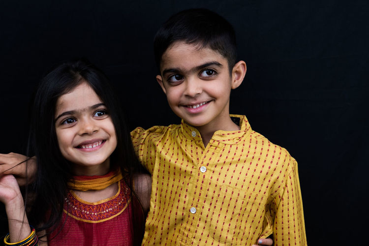 Close-up smiling siblings against black background
