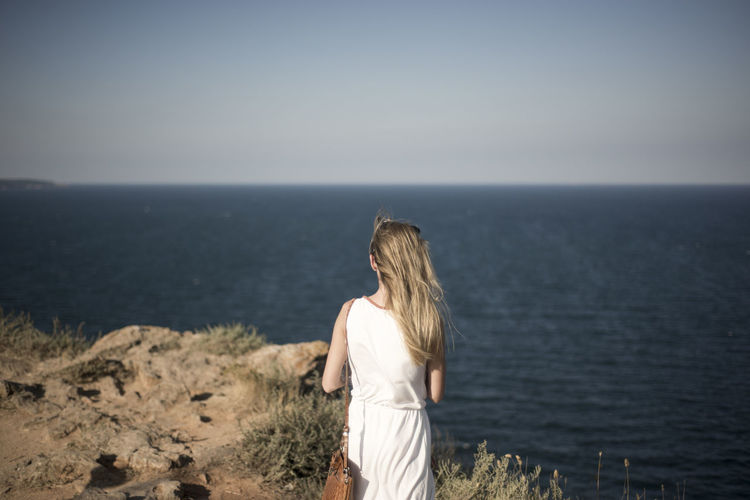 Rear View Of Woman Standing In Front Of Sea