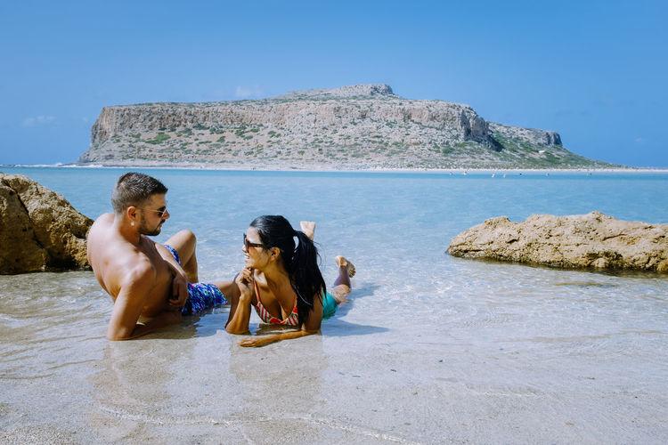 Men sitting on rock by sea against sky