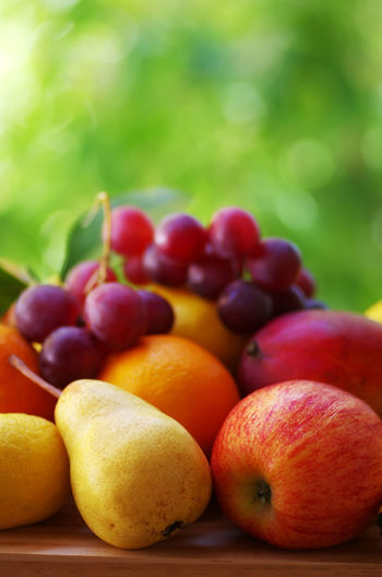 mixed fruits on table, green background Apple Apple - Fruit Close-up Food Food And Drink Freshness Fruit Grape Healthy Eating Red Ripe