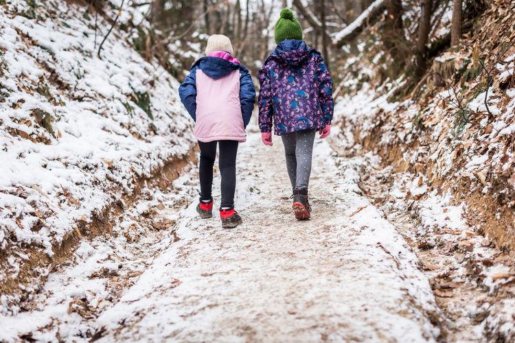 Rear view of women walking in snow