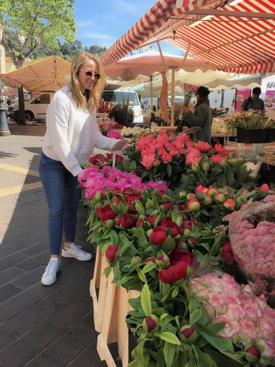 Woman standing by potted plants at market stall