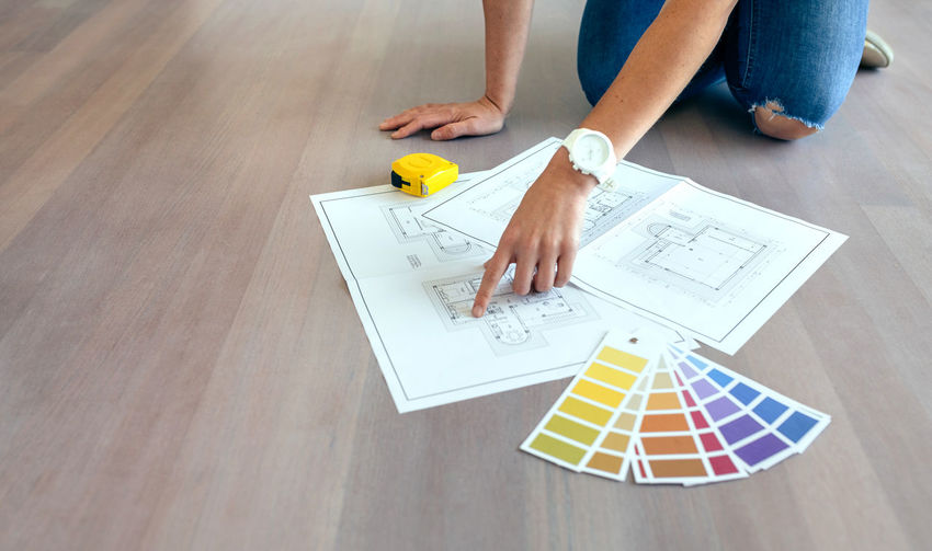 Woman with blueprint and color swatch on hardwood floor at home