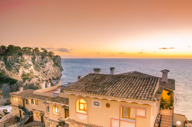 High Angle View Of Houses By Sea Against Sky During Sunset