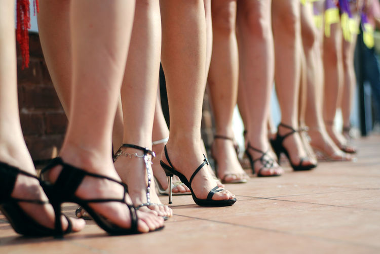 Low section of women wearing high heels while standing at fashion show
