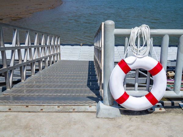 White and red lifebuoy hanging on the fence in the port near the sea. Water Railing Day Security No People Protection Sea Nature Safety Life Belt Outdoors Seat Bench Architecture White Color Tubing Absence Close-up Rescue Inflatable  Lifering Lifebuoy Port Beach Walkway