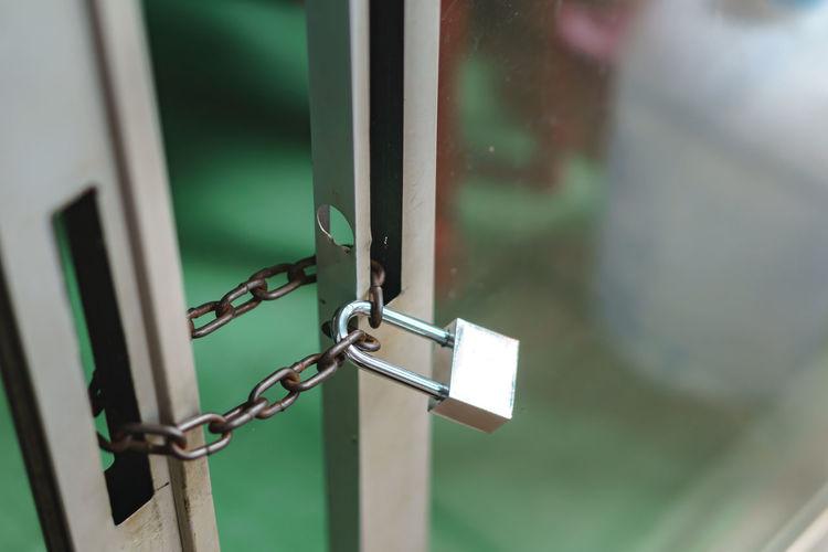 Close-up of padlock on glass door