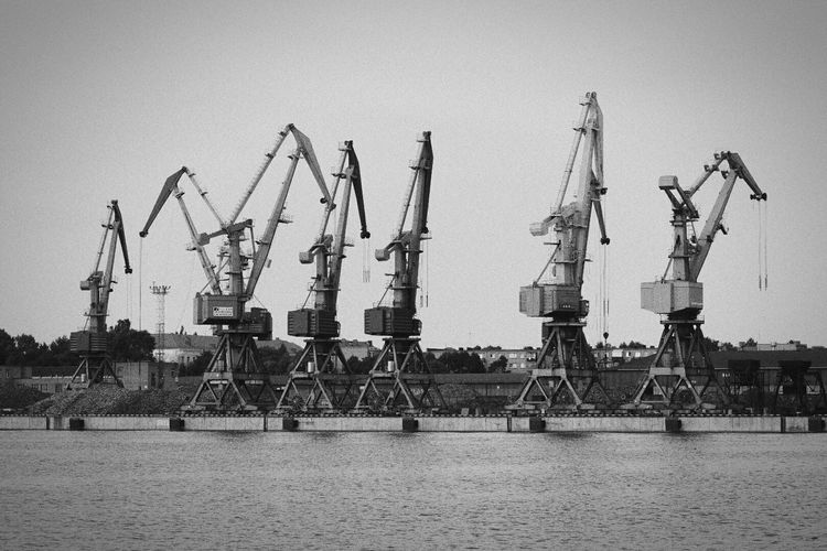 Cranes in shipping dock at sea against sky
