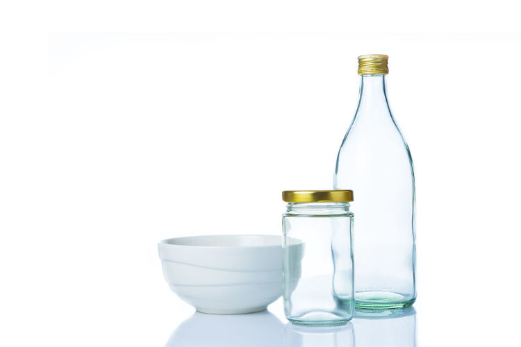 Glass jars and bottles and white bowl containers with lids on white background Isolated Backgrounds Bottle Bowl, Dish, Close-up Containers, Freshness Jars, No People White White Background