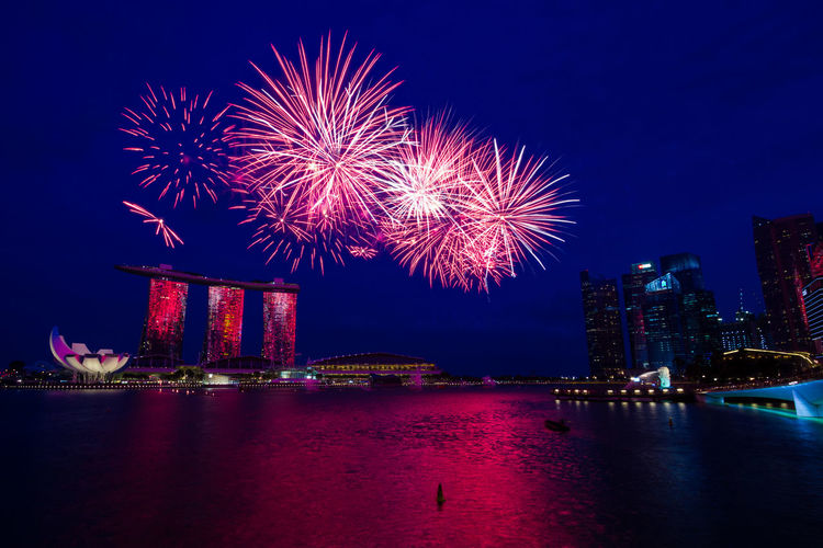 Low angle view of firework display over marina bay sands and river at night