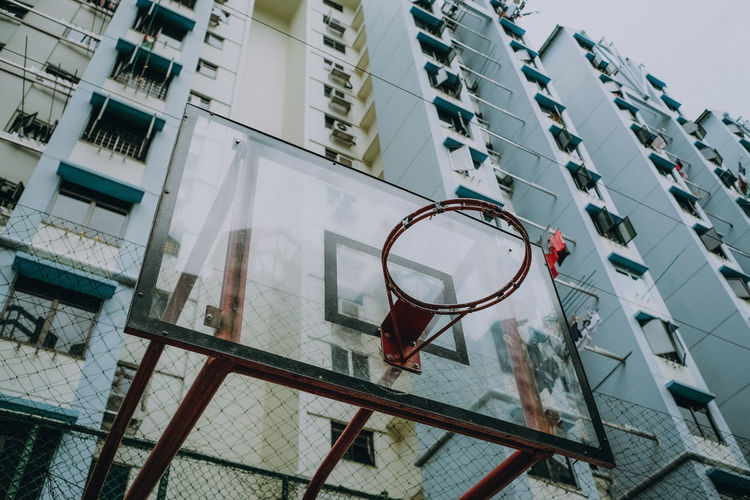 Low angle view of basketball hoop against buildings