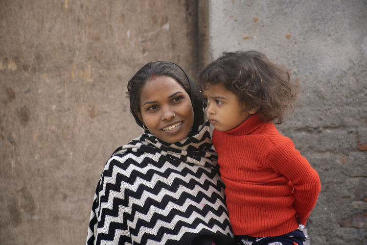 Smiling mother carrying daughter against wall