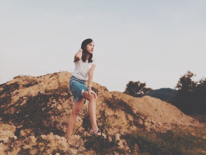 Full Length Of Young Woman Standing On Rock