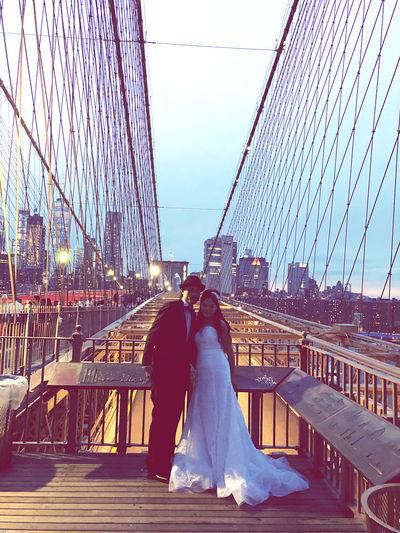 Rear view of friends on bridge against sky