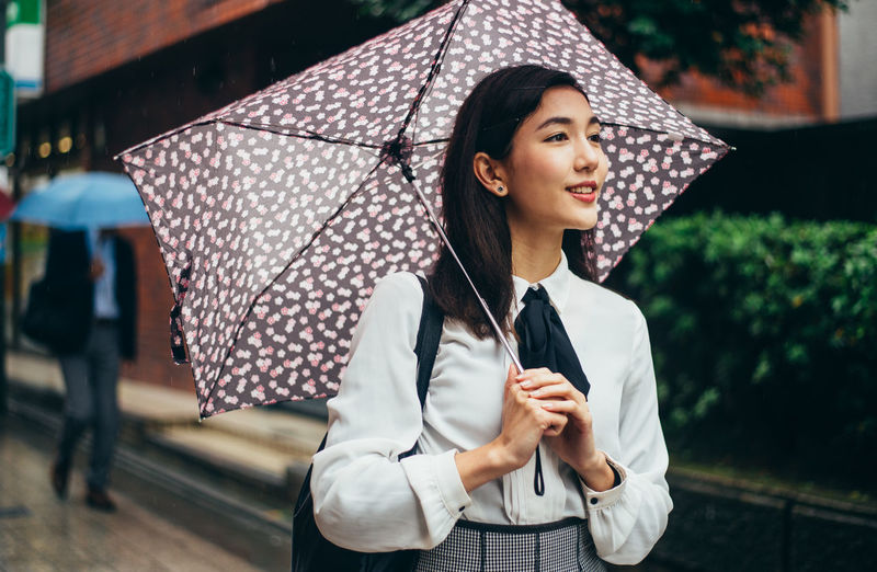 Beautiful young woman looking away while standing outdoors during rain
