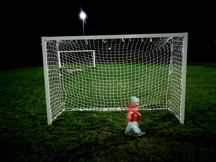 Low angle view of playing soccer on field at night