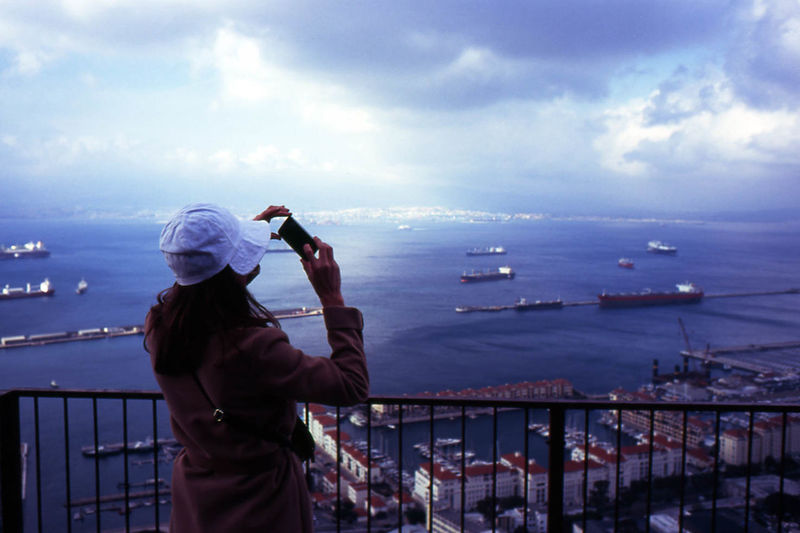 Rear view of woman photographing sea using phone against cloudy sky at dusk