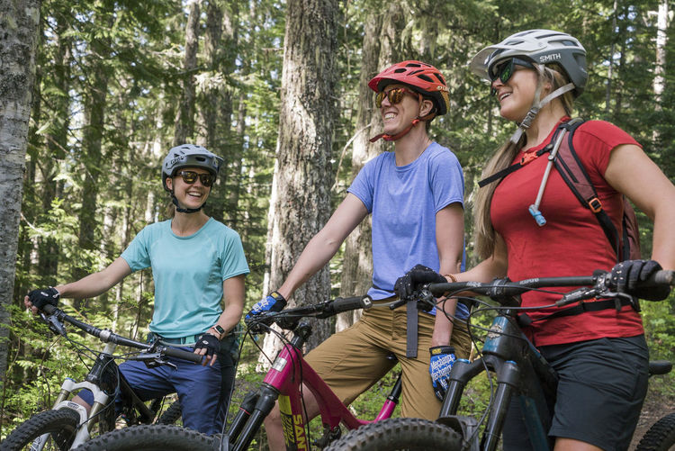 Smiling woman riding bicycle in forest