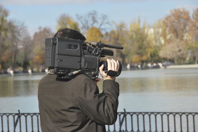 Rear view of man videographing while standing by lake