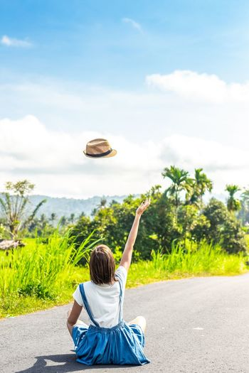 Rear View Of Woman Levitating Hat While Sitting On Road Against Sky