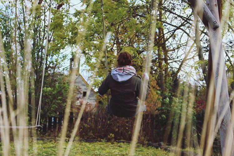 Rear view of woman sitting on swing in yard
