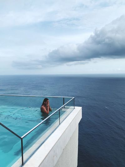 Woman in swimming pool by sea against sky