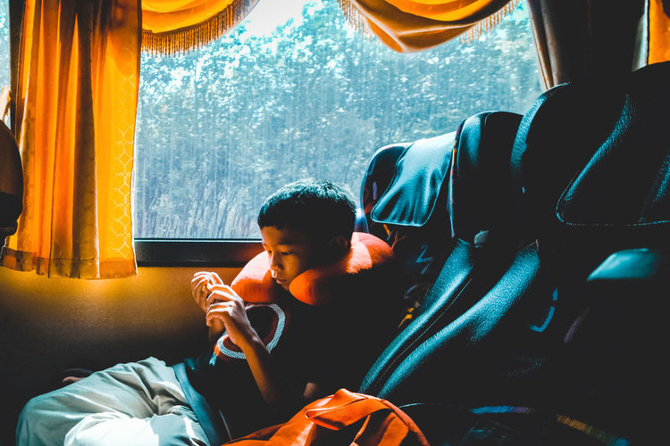 Boy watching video while sitting in bus