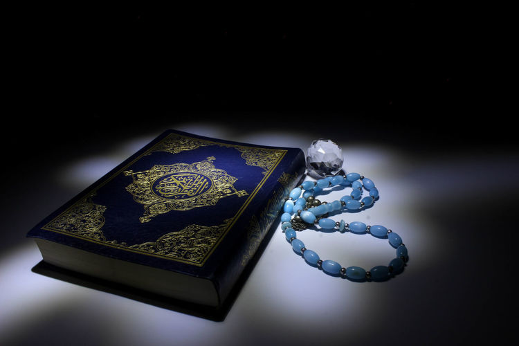 Quran Art And Craft Black Background Blue Book Close-up Gemstone  High Angle View Holy Indoors  Jewelry Luxury Metal Necklace No People Precious Gem Religion Representation Single Object Still Life Studio Shot Table Wealth