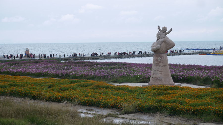 Statue by sea against sky